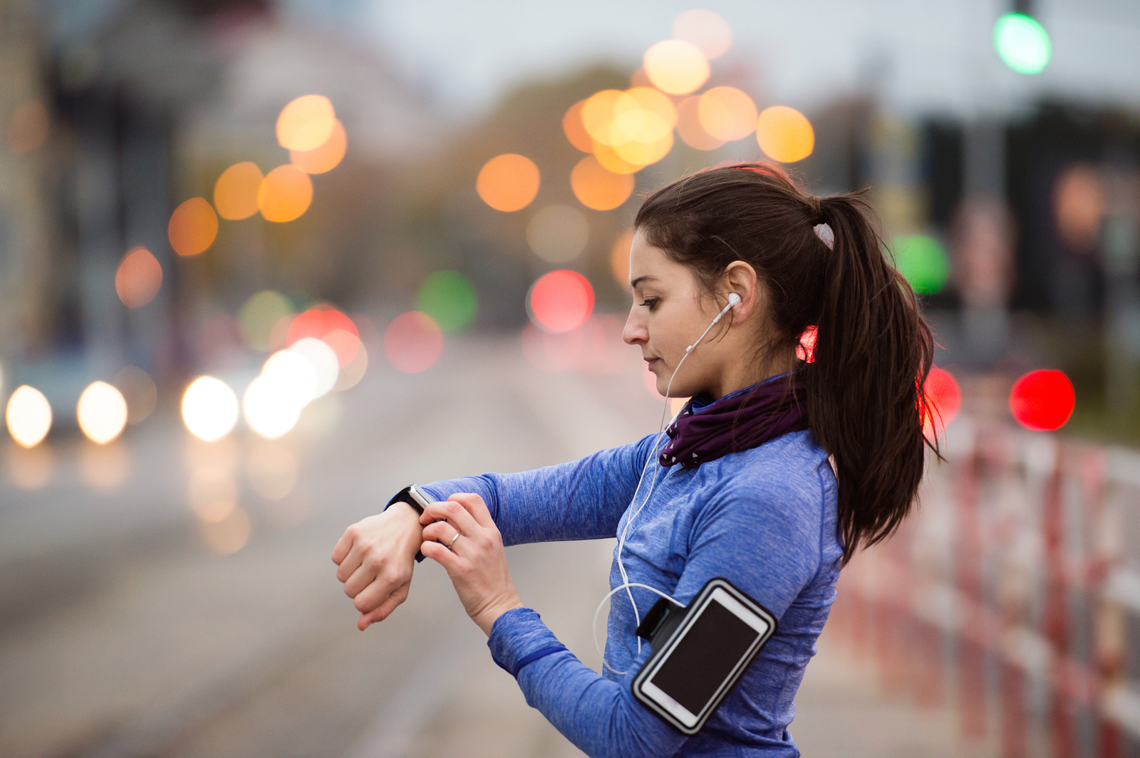 Beautiful young woman in the city with smart phone, smartwatch and earphones, listening music. Using a fitness app for tracking weight loss progress, running goal or summary of her run.