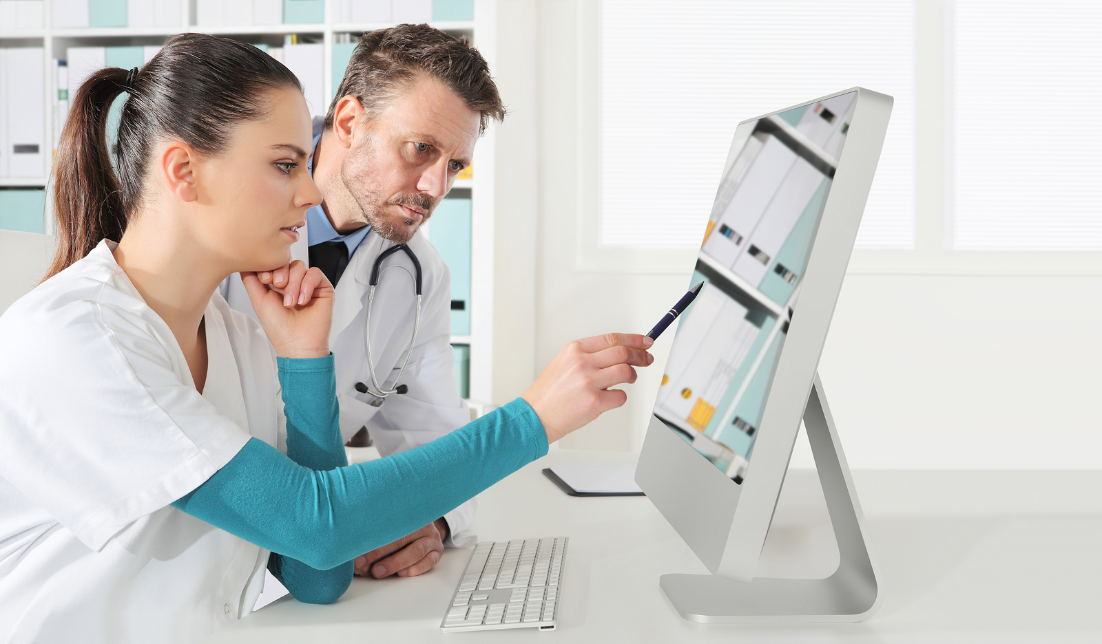 Doctor and nurse review patient information on remote population management technology platform