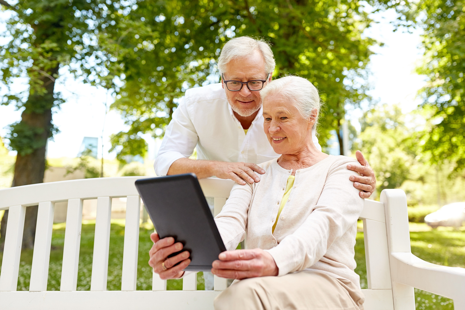 Senior couple outside using m.Care tablet to speak with care team