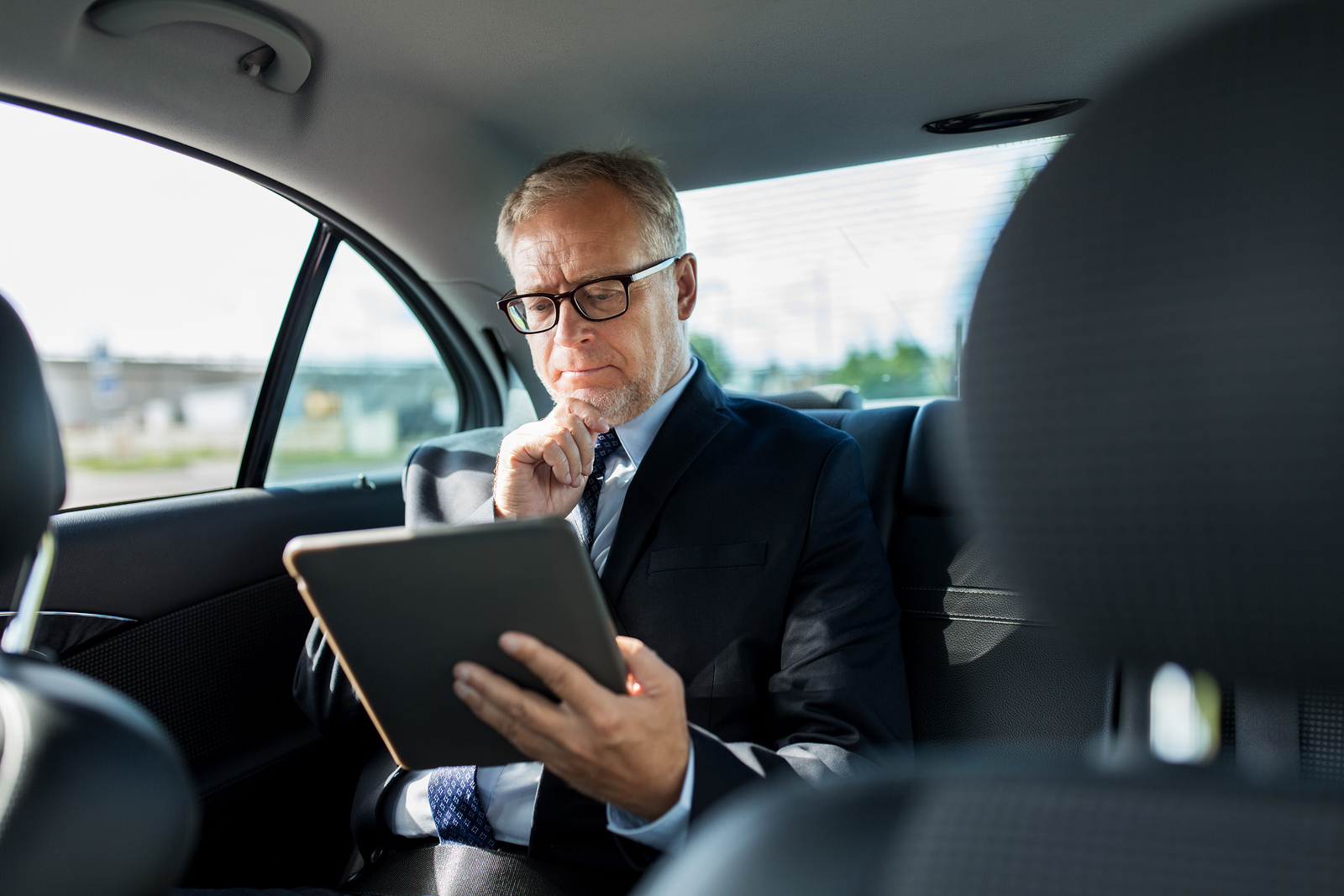Businessman using m.Care tablet while traveling in back seat of car