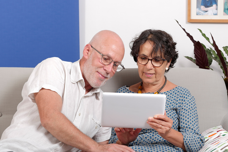 A senior couple using a tablet and smiling