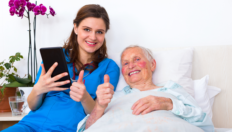 Doctor and senior patient showing thumbs-up at the nursing home using digital tablet.