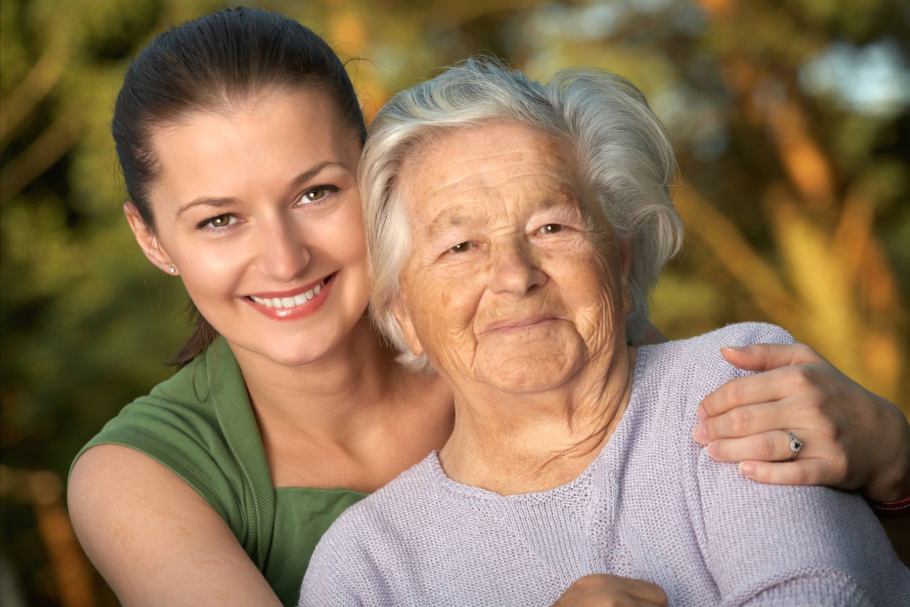 Young female caregiver hands hugging old woman
